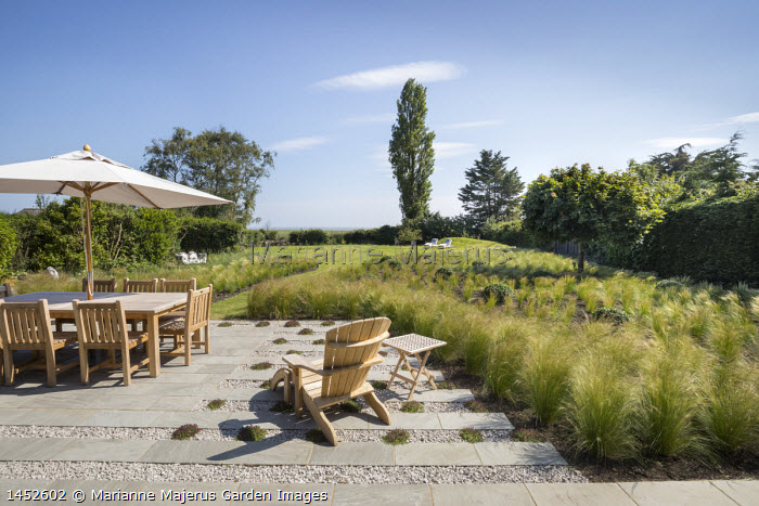 Table and chairs under umbrella on stone and gravel terrace outside interspersed with thyme, drift of Stipa tenuissima