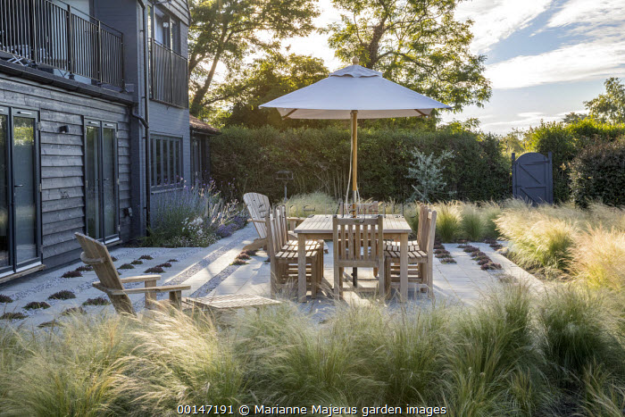 Table and chairs under umbrella on stone and gravel terrace interspersed with thyme, drift of Stipa tenuissima