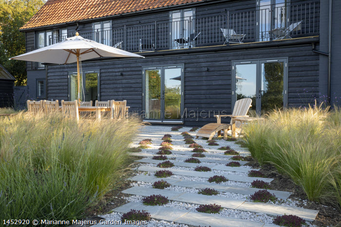 Wooden table and chairs under umbrella on gravel and stone terrace interspersed with thyme, Stipa tenuissima