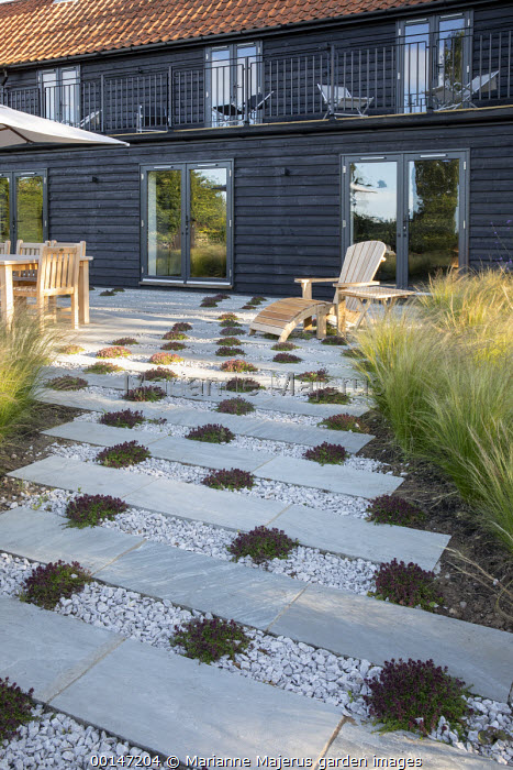 Wooden chair on gravel and stone terrace interspersed with thyme, Stipa tenuissima