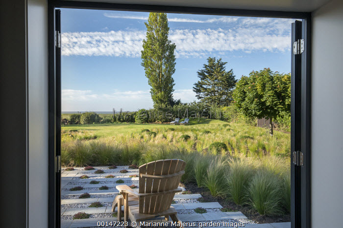 Framed view from inside house through doorway to wooden chair on stone and gravel terrace outside interspersed with thyme, drift of Stipa tenuissima