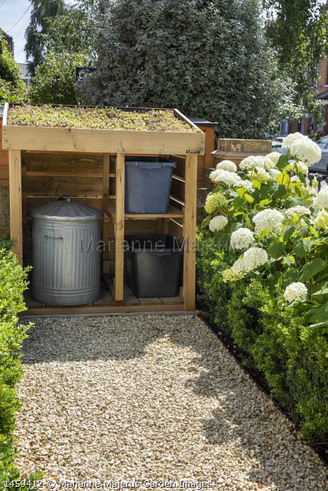 Rubbish bin storage with living green sedum roof in front garden, gravel path, hydrangea