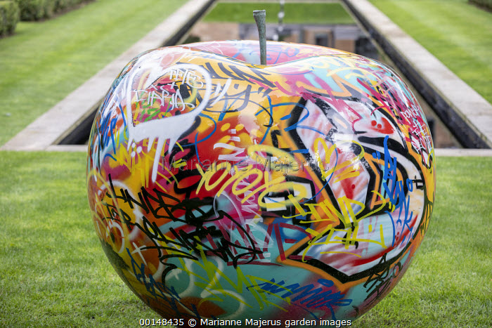 Contemporary apple graffiti sculpture by Andrew Martin on lawn