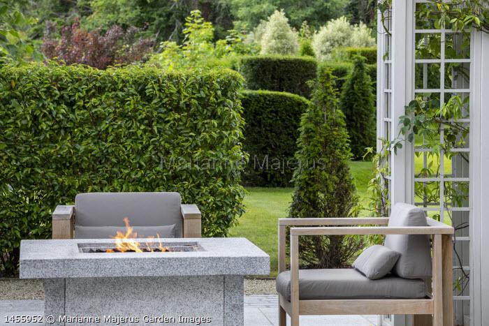 Contemporary chairs around granite stone firepit on terrace, Prunus lusitanica hedge