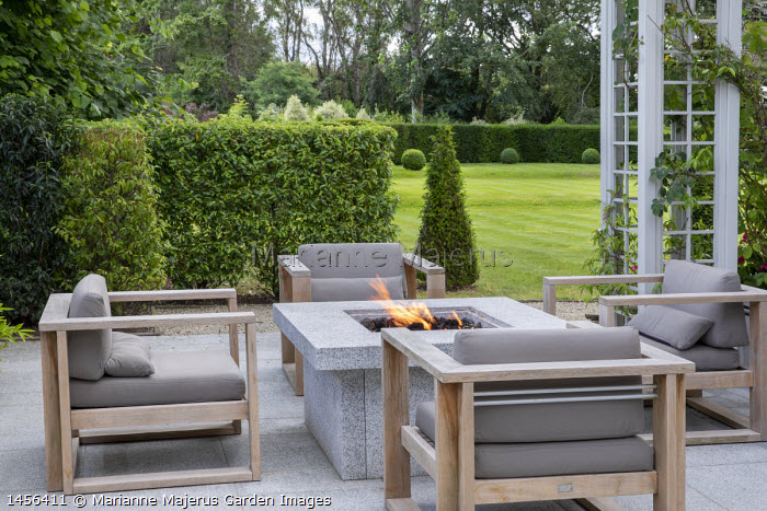 Contemporary firepit surrounded by chairs on patio, Prunus lusitanica hedge