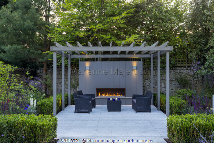 Clipped Buxus sempervirens hedge, stone paving, grey painted pergola, outdoor fireplace, sofas and table