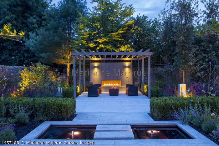Umbrella trained pleached Platanus × acerifolia trees over terrace, clipped Buxus sempervirens hedge, Verbena bonariensis, stepping stones over pond, stone paving, grey painted pergola, outdoor fireplace, sofas and table