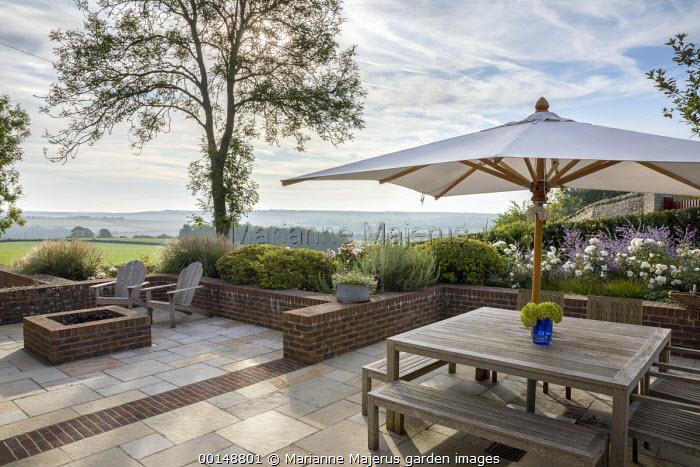 Wooden table and benches under umbrella on stone patio, brick walls, Rosa 'Iceberg', Perovskia 'Blue Spire'