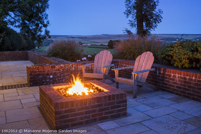 Wooden Adirondack chairs on patio by square brick firepit
