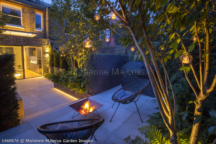 Contemporary chairs and firepit on Jura Limestone patio, sliding glass doors, multi-stemmed Prunus 'Kanzan', view into kitchen inside, hanging candle lanterns