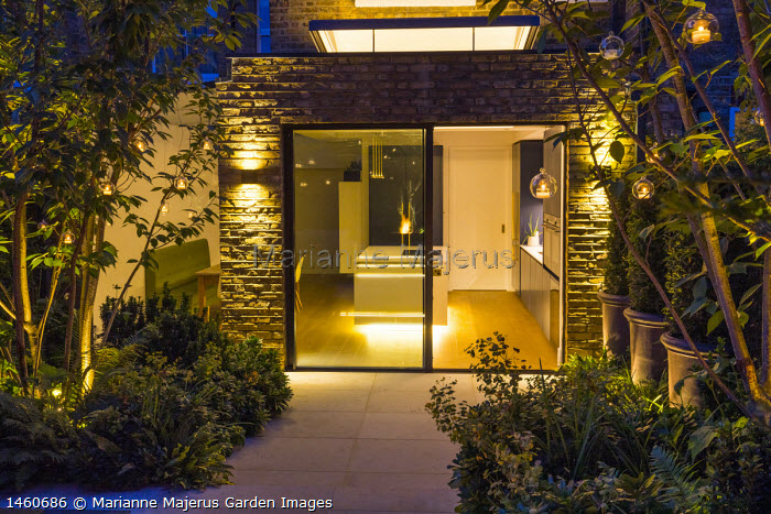 Contemporary stone patio, sliding glass doors, multi-stemmed prunus, view into kitchen inside, hanging candle lanterns