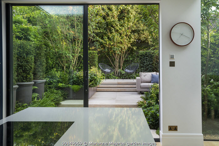 View from inside contemporary kitchen to courtyard garden outside, chairs on stone patio