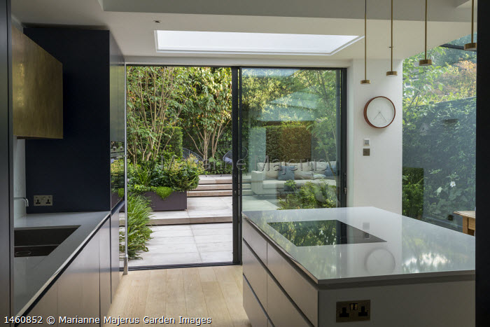 View from inside contemporary kitchen to courtyard garden outside