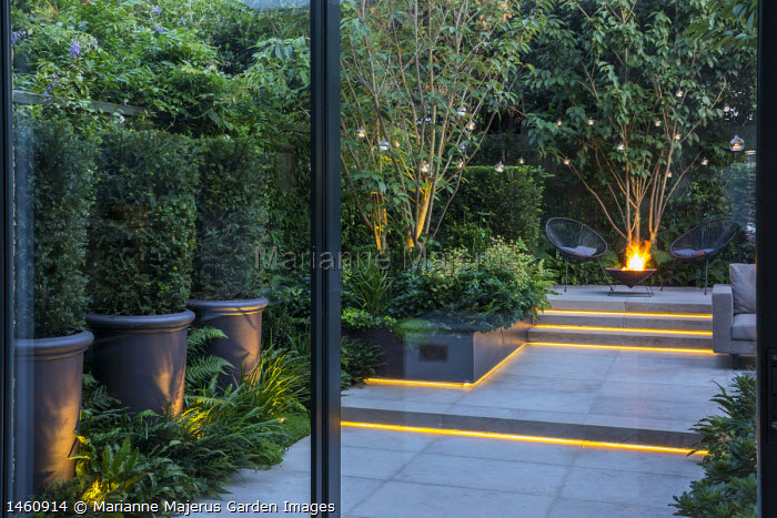 Multi-stemmed prunus in raised bed, Taxus baccata columns in pots, euphorbia, ferns, chairs on stone patio by brazier, hanging candle lanterns