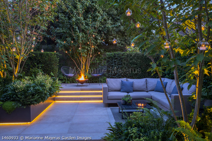 Multi-stemmed prunus in raised bed, euphorbia, ferns, chairs on stone patio by brazier, outdoor sofa with cushions, hanging candle lanterns