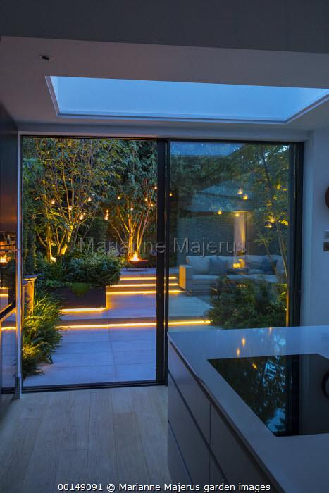 View from inside contemporary kitchen to courtyard garden outside, chairs and brazier on stone patio, hanging candle lanterns