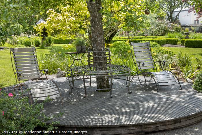 Chairs on circular decking around tree, metal tree seat