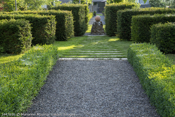 Clipped yew and box hedges, stepping stone and gravel path across lawn leading to circular sphere