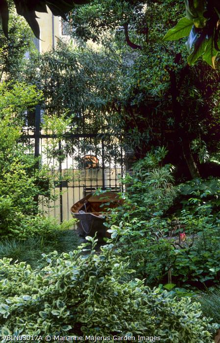 Boat by gate in shady garden