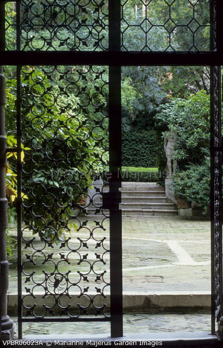 View through cast iron gate with Brandolini scorpion motif to courtyard and garden