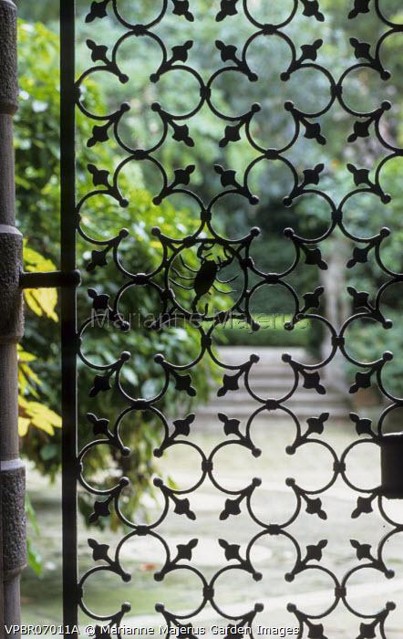 View through cast iron gate with Brandolini scorpion motif to courtyard and garden