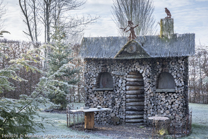 Wooden log house in hornbeam hedge enclosure