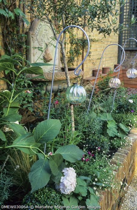 Raised bed with hydrangea, roses, Erigeron karvinskianus, Alchemilla mollis, olive tree, hanging candle lanterns, wall mounted basin
