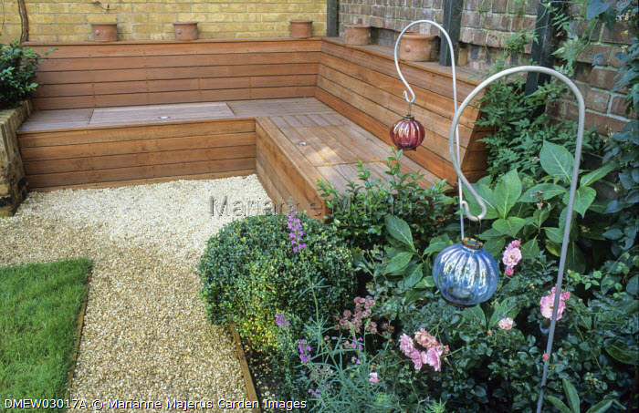 Gravel path, roses, built-in wooden bench with hidden storage against courtyard wall, lanterns