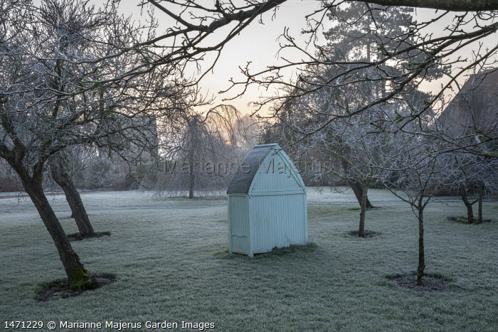 Wooden arbour in orchard, frost on lawn