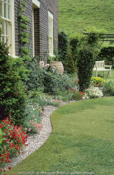 Neatly cut curving sinuous lawn edge, bench, alpines in gravel border