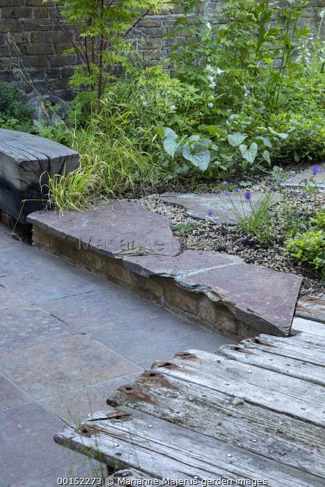 Charred wooden bench, Milium effusum, Brunnera macrophylla 'Jack Frost', Geranium 'Johnson's Blue', stepping stone path, reclaimed timber decking, stone patio