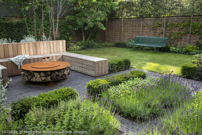 Built-in wooden seating area around Cor-Ten steel firepit with log storage, low Taxus baccata hedge, herb border with Lavandula angustifolia 'Hidcote Blue', Rosmarinus officinalis 'Miss Jessopp's Upright', Teucrium fruticans, view to green bench by lawn