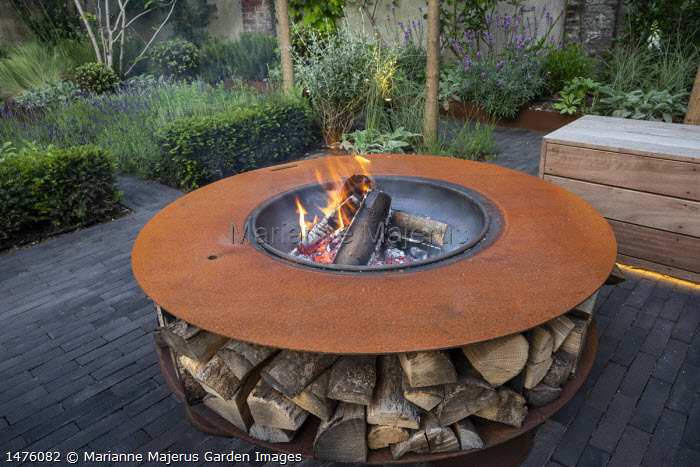 Cor-Ten steel firepit with log storage, low clipped Taxus baccata hedge, lavender