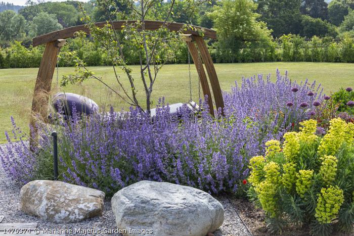 Timber-framed swinging daybed with purple cushions, Nepeta racemosa 'Walker's Low', Allium hollandicum 'Purple Sensation', Euphorbia characias subsp. wulfenii, large rocks