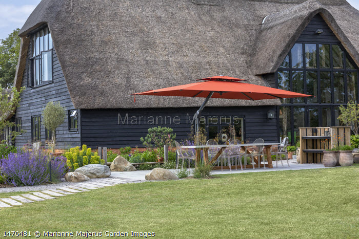 Transparent chairs around table on stone patio under orange umbrella, Stipa gigantea, Nepeta racemosa 'Walker's Low', Euphorbia characias subsp. wulfenii, timber sleeper path across gravel, large rocks, thatched converted barn