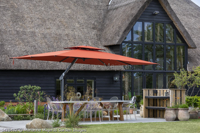 Transparent chairs around table on stone patio under orange umbrella, Stipa gigantea, Nepeta racemosa 'Walker's Low', large rocks, thatched converted barn