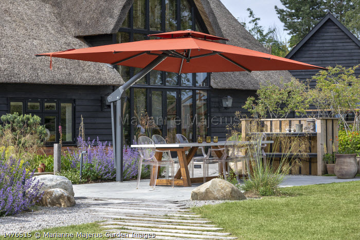 Transparent chairs around table on stone patio under orange umbrella, Stipa gigantea, Nepeta racemosa 'Walker's Low'