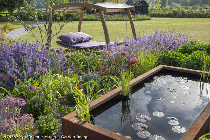Timber-framed swinging daybed with purple cushions, Nepeta racemosa 'Walker's Low', Allium hollandicum 'Purple Sensation', Allium cristophii, raised Cor-Ten steel pond
