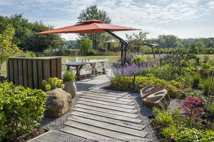 Transparent chairs around table on stone patio under orange umbrella, Nepeta racemosa 'Walker's Low', wooden sleeper path