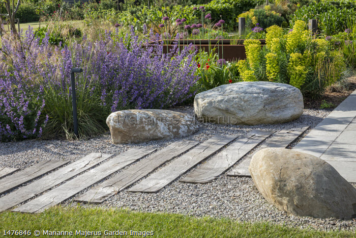 Large rocks, Nepeta racemosa 'Walker's Low', Allium hollandicum 'Purple Sensation', Euphorbia characias subsp. wulfenii, timber sleeper path across gravel, raised Cor-Ten steel pond