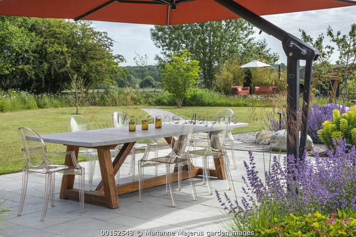 Transparent chairs around table on stone patio under orange umbrella, Nepeta racemosa 'Walker's Low', Stipa gigantea, Euphorbia characias subsp. wulfenii