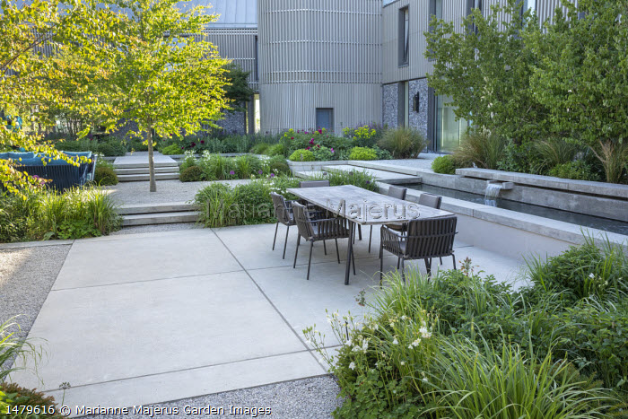 Concrete water shutes in formal pool, concrete steps, table and chairs on concrete terrace, Cercidiphyllum japonicum