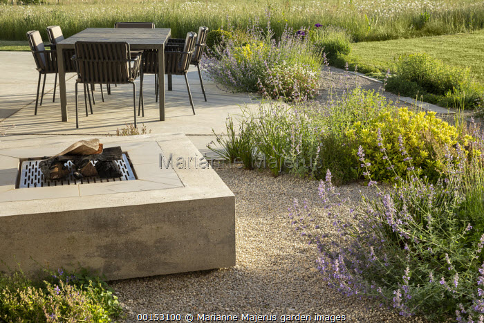 Table and chairs on terrace by concrete firepit, Nepeta racemosa 'Walker's Low', Pittosporum tobira 'Nanum', Campanula portenschlagiana