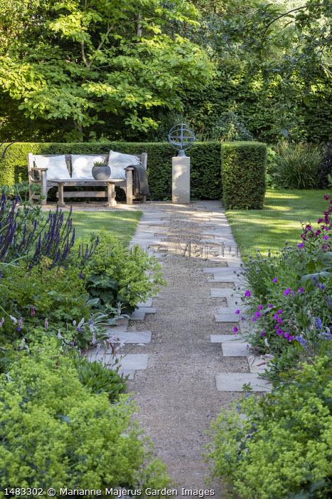 View along gravel and stone path towards bench in yew hedge enclosure, Alchemilla mollis, Salvia nemorosa 'Caradonna', Geranium 'Patricia', Persicaria bistorta 'Superba'