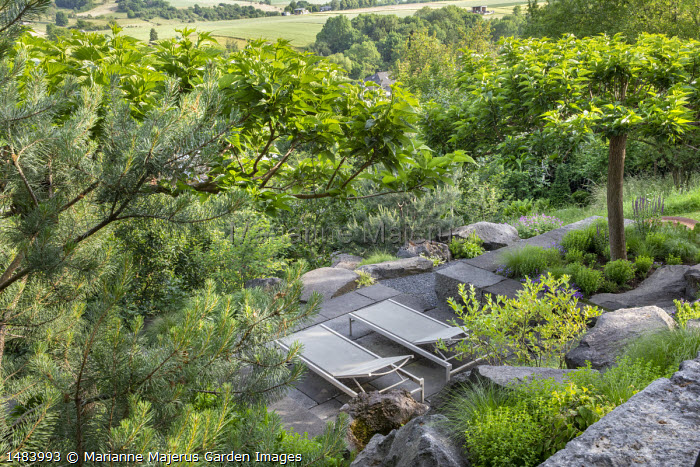 Recliner chairs on stone terrace in sloping rock garden, large rocks