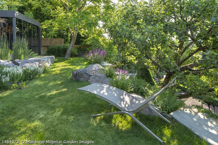 Recliner chair by ferns on lawn under apple tree, large rocks, Salvia nemorosa 'Adrian'