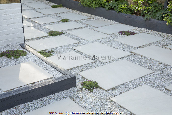 Stone paving slab and gravel terrace interspersed with thyme, black timber edging