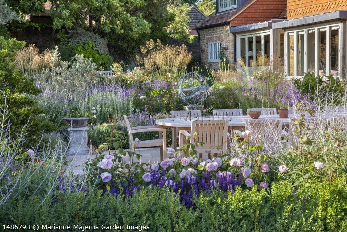 Wooden table and chairs on stone patio, Rosa 'Olivia Rose Austin', Perovskia 'Blue Spire', Salvia nemorosa 'Caradonna', Stipa gigantea, armillary sphere