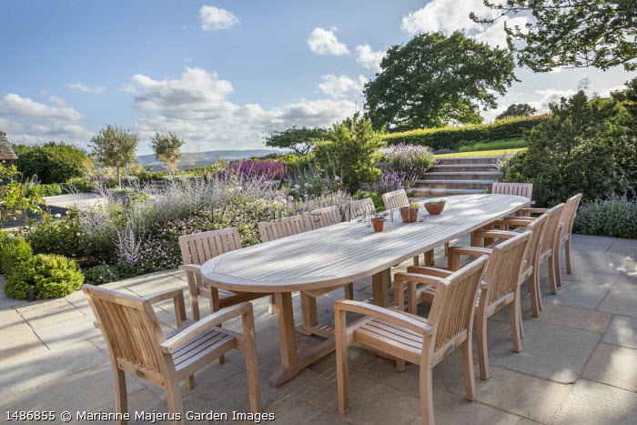 Wooden table and chairs on stone patio, Perovskia 'Blue Spire', Geranium 'Dreamland'