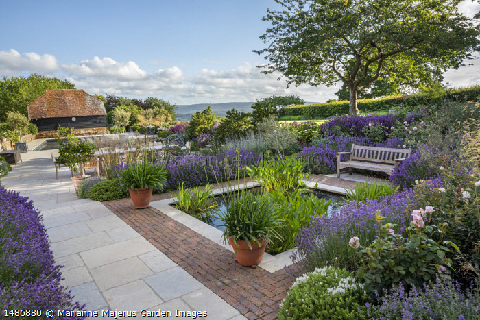 Wooden bench on stone and brick patio overlooking square formal pond, agapanthus in terracotta pots, Lavandula angustifolia 'Munstead', Rosa 'The Alnwick Rose', Rosa 'Olivia Rose Austin'